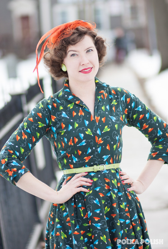 Retro 1950s inspired outfit with a space ship and flying saucer novelty print flannel dress paired with a bright orange feathered hat