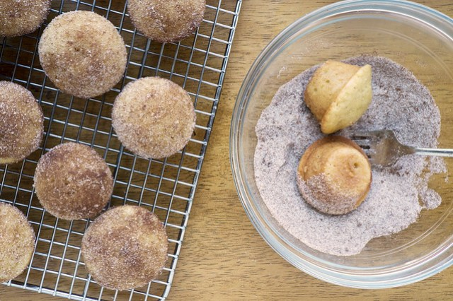 rolling the muffins in cinnamon-sugar