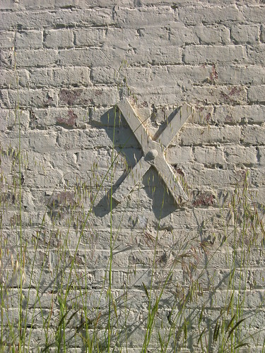 A brick wall with a metal X in the middle of it. Cream coloured paint has been used to liberally cover both.