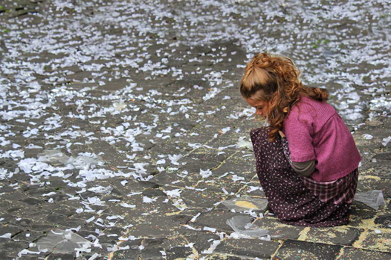 A little girl looking at wedding confetti