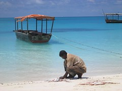 Mosi, my spearfishing guide, guts the catch of the day on the white sands of Zanzibar