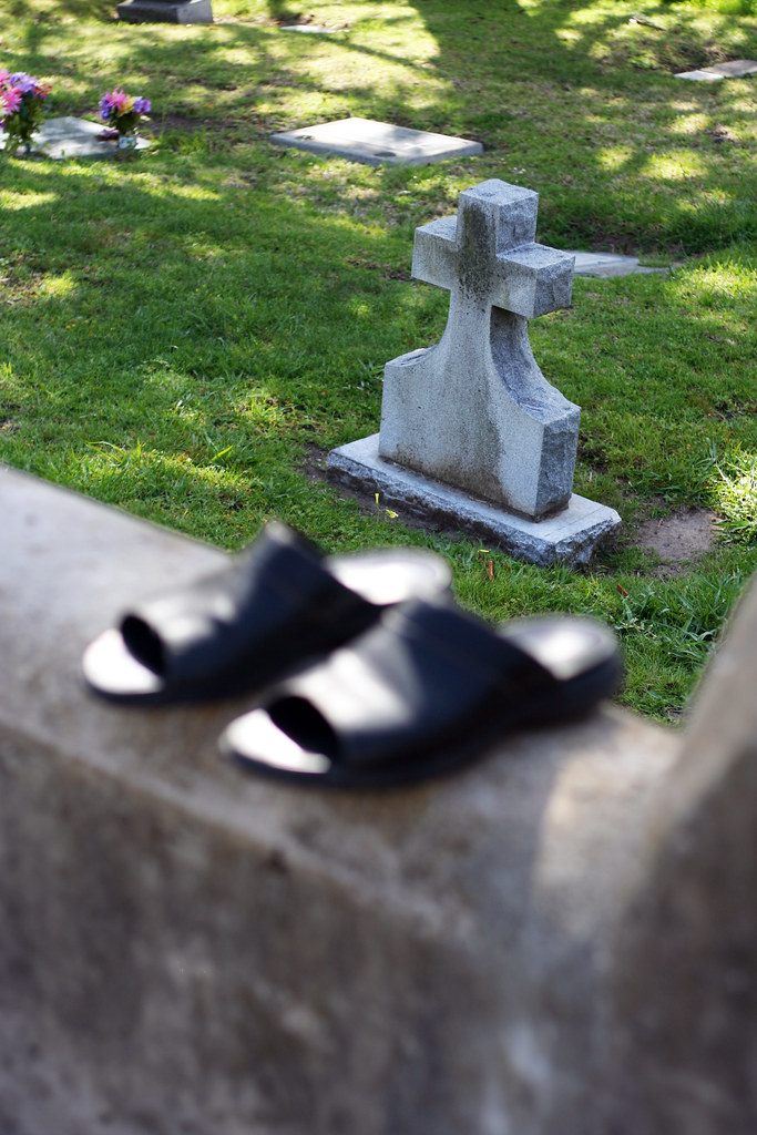 a pair of abandoned shoes near a headstone