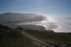 A couple walking on a Pacific Ocean beach, mis...