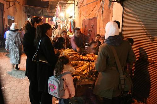 Photo de gens qui achètent le maïs grillés à Derb Dabachi rue dans l'ancienne Médina de Marrakech