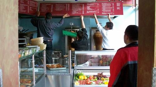 Die Mitarbeiter des neuen türkischen Restaurants hängen die Preistafel auf.