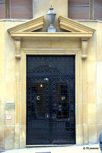 Portal del número 6 de la calle Estella, sede de Cementos Portland, cuyas iniciales pueden verse en la puerta.