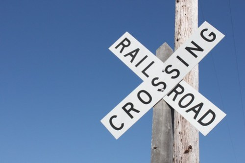 A railroad crossing sign against a blue sky.