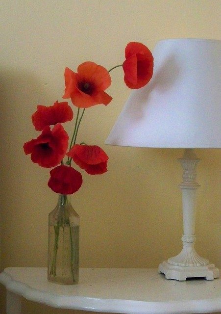 Glass vase of red poppies on white table with lamp in yellow room