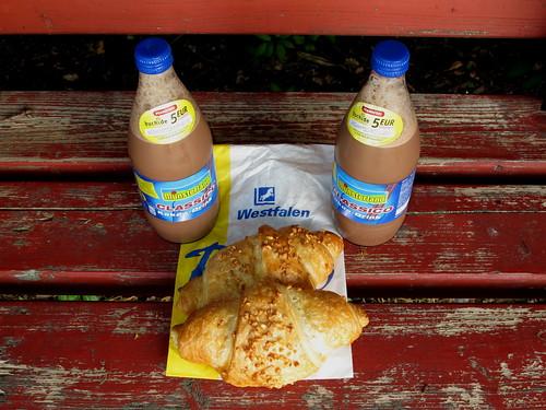 Marzipancroissant und Kakao zum Frühstück auf einer Bank