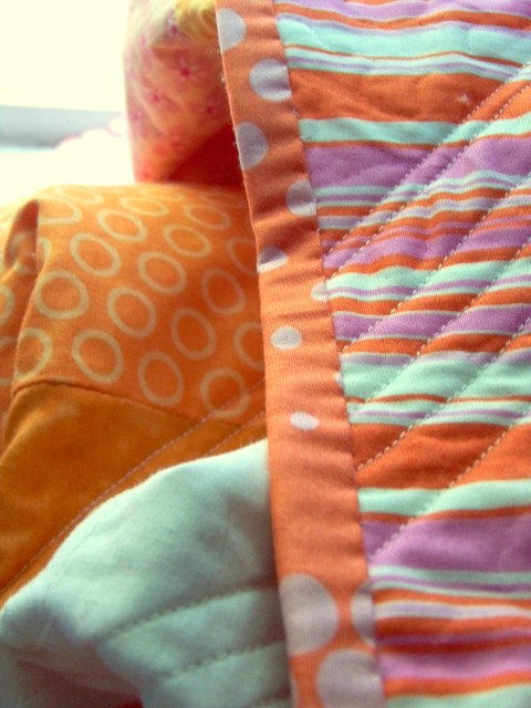 detail - strightline quilting on striped back and polka dot pink orange quilt binding