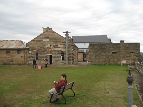 Tom having a rest with the Mess Hall and Barracks behind