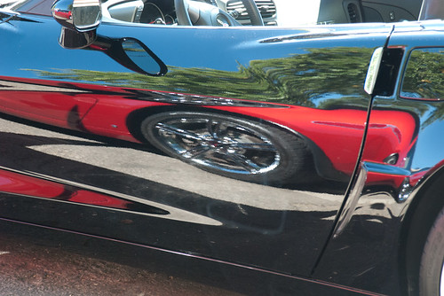 Red Corvette Reflected On A Black One