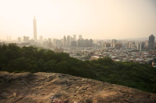 The Taipei City Skyline and Taipei 101 and a swastika carved into a rock