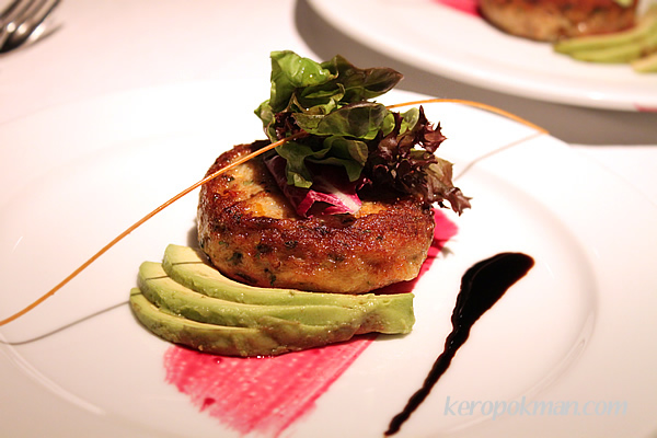 Crabmeat cake with avocado topped with musclun salad, beetroot paint and balsamic reduction