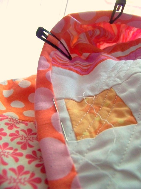 hand stitching binding on pink and orange quilt