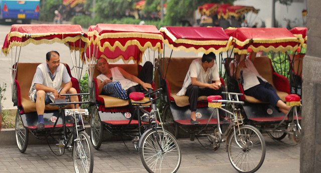 Pedicab drivers distracting themselves from boredom with cell phones