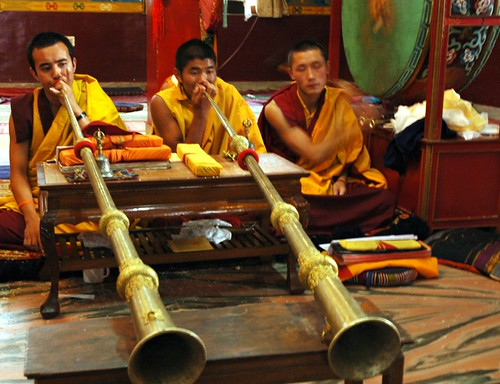 Tibetan Buddhist monks blowing the long horns,...