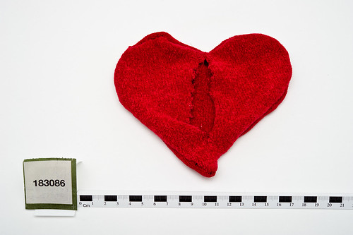 a heart made with red plastic and has a cut (originally contained message)