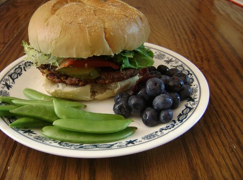 Black Bean Burger with salad greens, tomato, pickles, ketchup, and Vegenaise; with sugar snap peas and blueberries