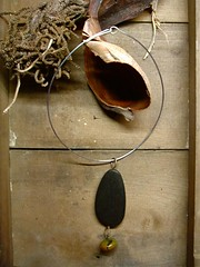 black wooden disk with a natural turquoise bead