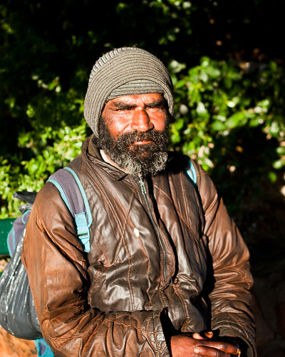 Homeless man sitting in the morning sun