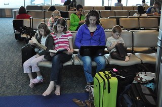 Young family waiting at airport gate -- Mom and three kids, all either reading or on computers.