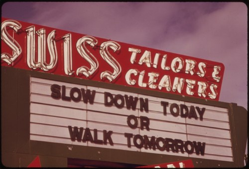 Unlighted Business Sign Reminds Motorists to Conserve Gasoline During the Fuel Crisis 12/1973