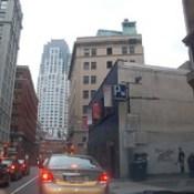 Banksy in Boston: View of F̶O̶L̶L̶O̶W̶ ̶Y̶O̶U̶R̶ ̶D̶R̶E̶A̶M̶S̶ CANCELLED on Essex St, Chinatown, Boston, with rush hour traffic