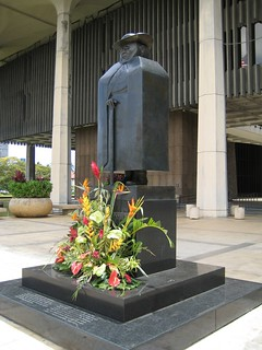 Father Damien statue outside of the Hawai'i State Capitol -- close-up shot of the blocky statue, two pillars of the Capitol building visible behind him.