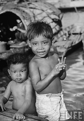 Saigon 1950 - Two brothers bathing in a river while peering into the distance.