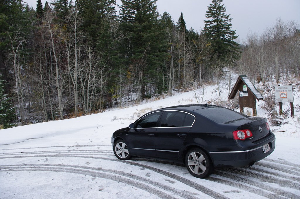 black sedan parked near a snowy mountain trail