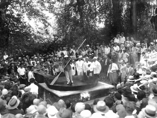 Crowd surrounding a woman skating around a giant skillet with slabs of bacon tied to her feet, holding a giant wooden spatula, Chehalis, Washington