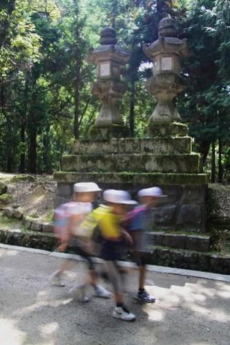 Children passing stone lanterns