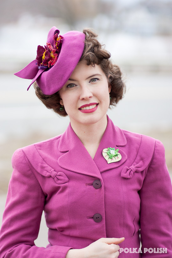 Pink 1940s suit paired with a flower-topped tilt hat and a green frog brooch