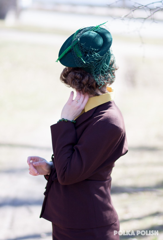 Green wool 1940s tilt hat with coarse veiling and a pair of crossed feathers, styled with green bakelite and a brown suit