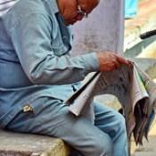 India - Uttar Pradesh - Mathura - Man Reading Newspaper.
