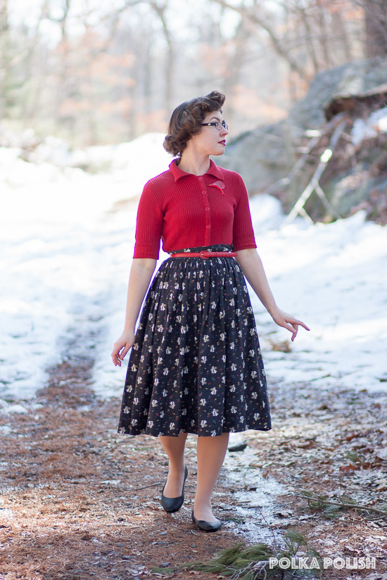 1950s inspired outfit featuring a red cardigan, black flats, and a black piano novelty print skirt