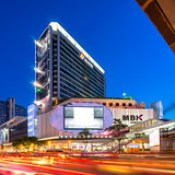 Panorama of MBK Center shopping mall in twilight time with traffic jam in Bangkok Thailand