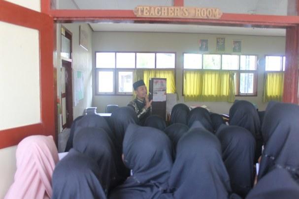 Para siswa mendengar arahan guru tengan ruang