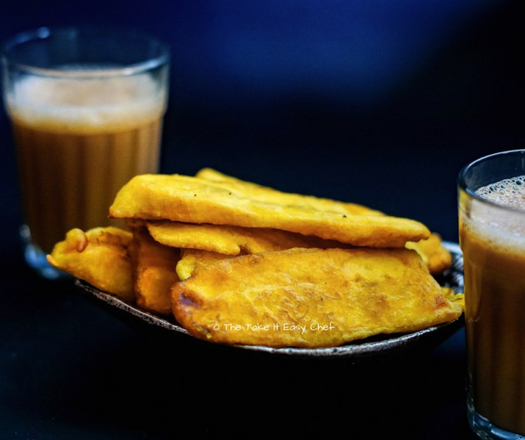 A plate of pazham pori with a glass of tea