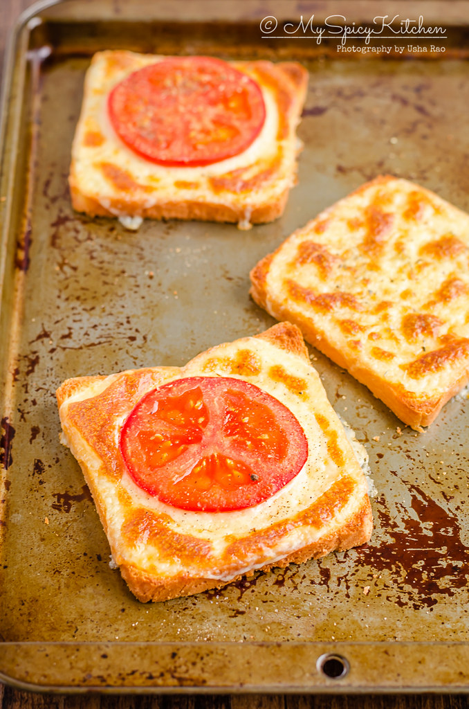 A slice of cheese toast and two slices of 3 ingredient tomato cheese toasts on a baking sheet