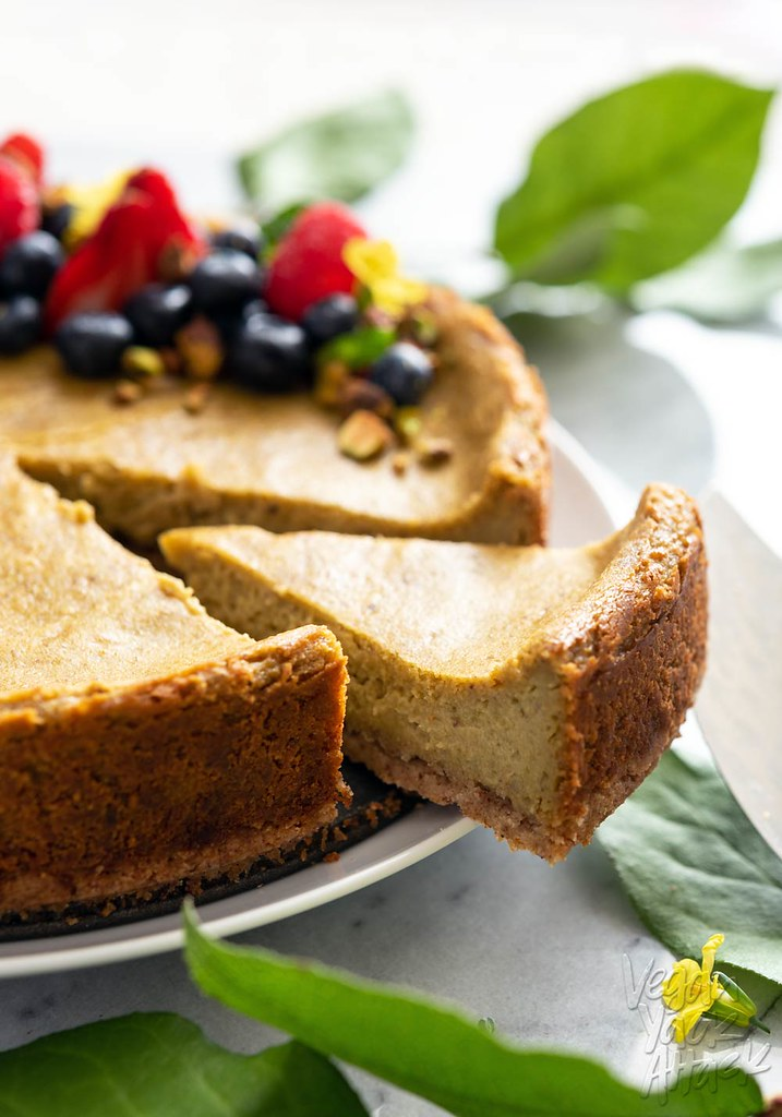 This Gluten-free Pistachio Cheesecake is light green in hue and straight up delicious. Plus, it's vegan! Top it with some seasonal berries for a pop in flavor and color. #vegan #glutenfree #veganyackattack #cheesecake
