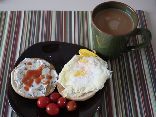 bagel with fried egg, cream cheese, hot sauce, grape tomatoes, coffee