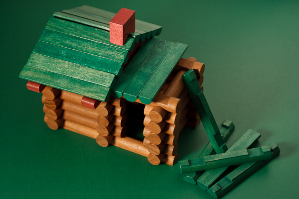 A green roofed Lincoln Log cabin, under construction.