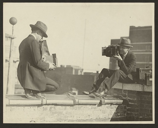 [Two photographers taking each others' picture with hand-held cameras while perched on a roof] (LOC)