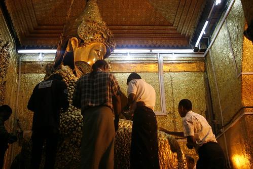 Hombres colocando láminas de oro a Buda