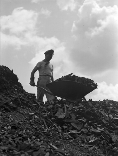Midvale Company operator Machion unloading a wheelbarrel full of charcoal at the Open Hearth Furnace Yard, July 1, 1946