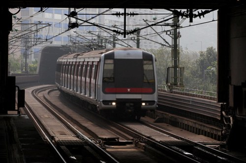 Northbound train arrives at Kwai Hing station: a sound-deadening tube encloses the line from Kwai Fong