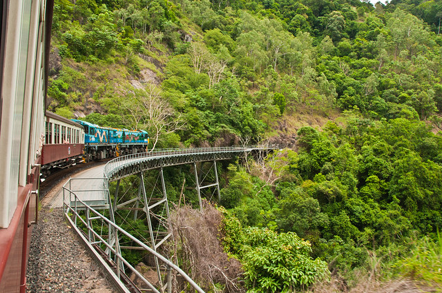 The Kuranda Railway on a curved bridge stuck to the side of a cliff