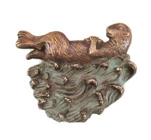 brass doorknocker has a sea otter resting on waves.